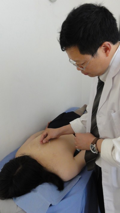 Dr Zhou putting acupuncture needles into patient's back