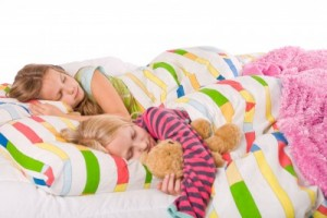 Two girls asleep on colorful bedding